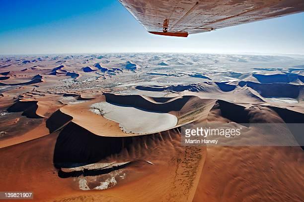 Aerial view of sand dunes at Sossusvlei in Namib desert. Wing tip visible of airplane. Namib Naukluft National Park, Namibia.