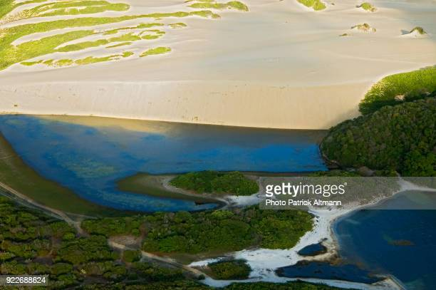Aerial view of sand dunes formation with swamps and tropical flora in Genipabu, Rio Grande Do Norte, Brazil