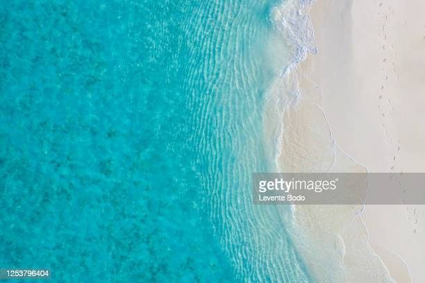 aerial view of sandy tropical beach in summer. aerial landscape of sandy beach and ocean with waves, view from drone or airplane. nature environment, peaceful bright zen, freedom scene - bay of water stock pictures, royalty-free photos & images