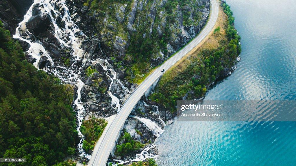 Luchtmening van schilderachtige bergweg met auto, overzees en waterval in Noorwegen : Stockfoto