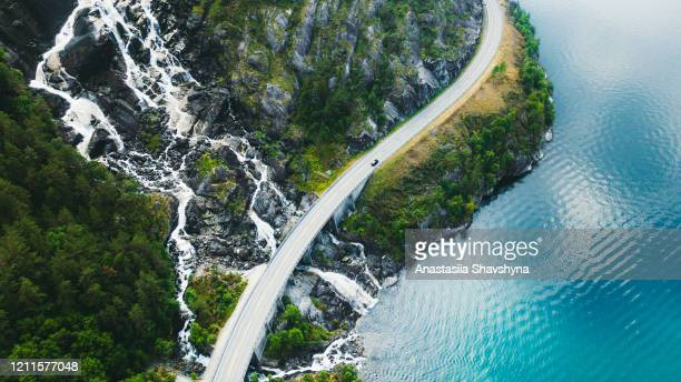 aerial view of scenic mountain road with car, sea and waterfall in norway - road stock pictures, royalty-free photos & images