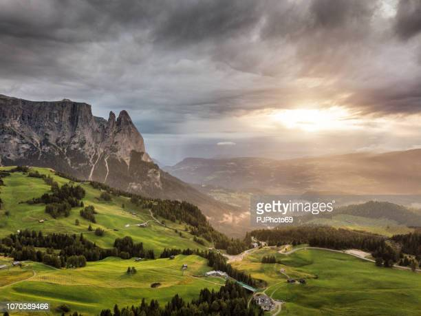 Aerial view of Sciliar mountains with sunlight and dramatic sky - Dolomites