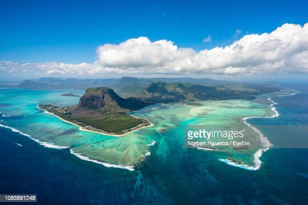 aerial view of sea against cloudy sky - mauritius stock photos and pictures