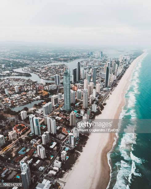 aerial view of sea and cityscape against sky - gold coast queensland stock pictures, royalty-free photos & images