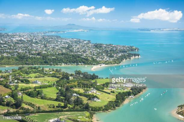 aerial view of sea and cityscape against sky - auckland stock pictures, royalty-free photos & images