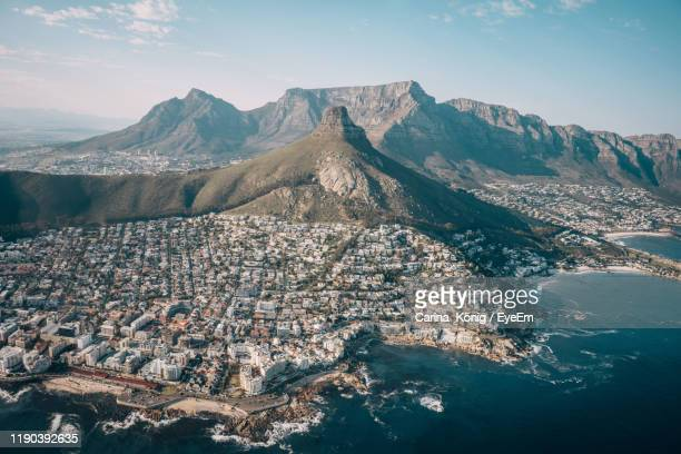 aerial view of sea and mountains against sky - table mountain stock pictures, royalty-free photos & images