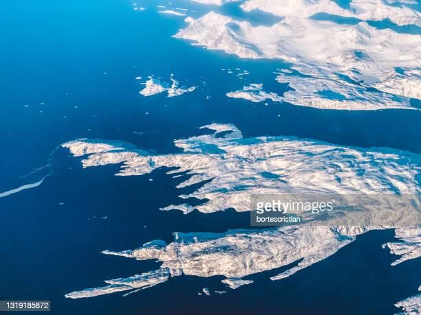 aerial view of sea and snowcapped mountains against blue sky - bortes fotografías e imágenes de stock
