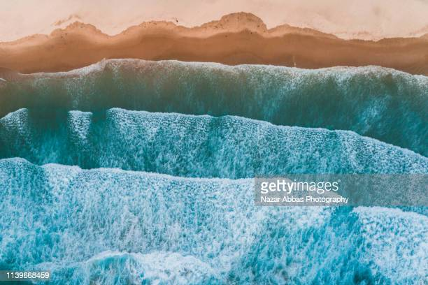 aerial view of sea waves breaking on shore. - riva dell'acqua foto e immagini stock
