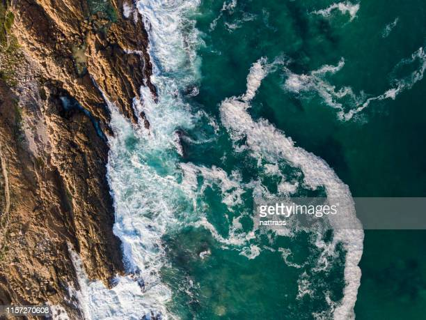 aerial view of sea waves crashing against rocky coast - rocky coastline stock pictures, royalty-free photos & images