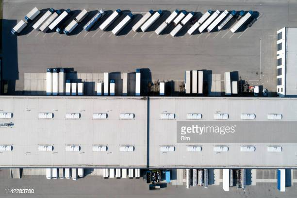 aerial view of  semi trucks and distribution warehouse - food distribution stock pictures, royalty-free photos & images
