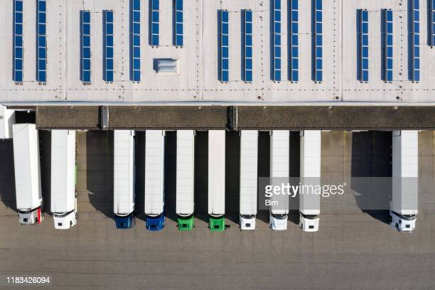 aerial view of semi-trucks loading at logistic center, distribution warehouse - sending stock pictures, royalty-free photos & images