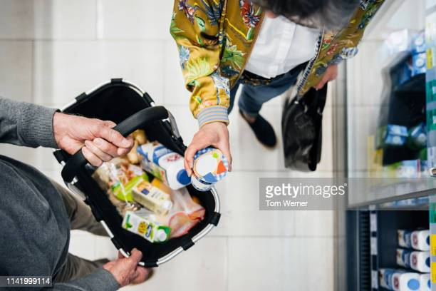 aerial view of senior couple picking out groceries - consumentisme stockfoto's en -beelden