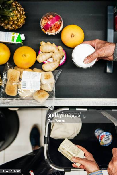aerial view of senior couple placing groceries on checkout conveyor - groceries stock pictures, royalty-free photos & images