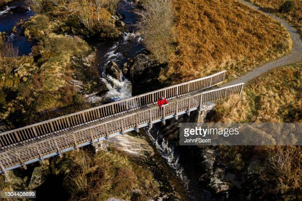aerial view of senior man on a rural footbridge - johnfscott stock pictures, royalty-free photos & images