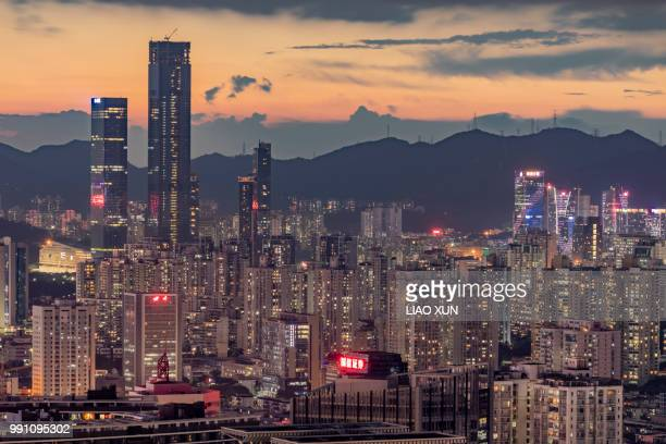 Aerial view of Shenzhen skyscrapers at dawn with a background of moutains