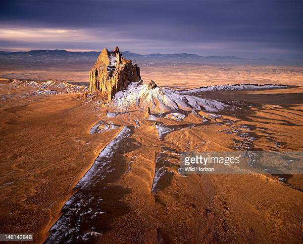 Aerial view of Shiprock at sunrise a monumental landform sacred to the Navajo people graced by a winter snowfall This is the American Southwest's...