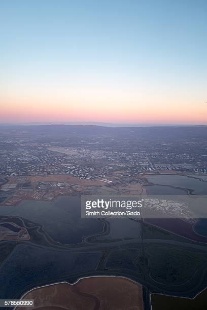 Aerial view of Silicon Valley at dusk including salt ponds on the San Francisco Bay and the towns of Santa Clara and San Jose with Levi Stadium...