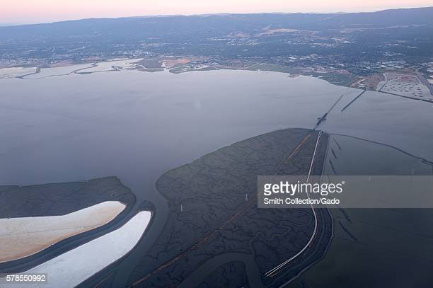 Aerial view of Silicon Valley at dusk, including the Dumbarton Bridge over the San Francisco Bay, and portions of the towns of Palo Alto, California,...