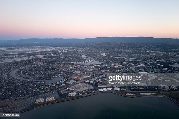 Aerial view of Silicon Valley at dusk, with a portion of the San Mateo/Hayward Bridge visible, as well as Foster City, including the California...
