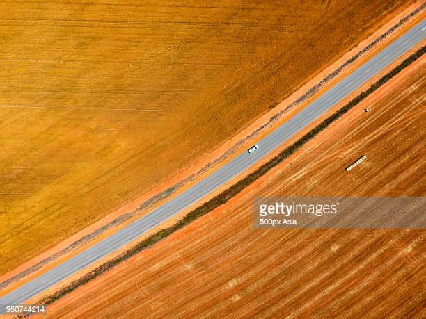 aerial view of single car driving on country road with fields on sides, australia - image stock pictures, royalty-free photos & images