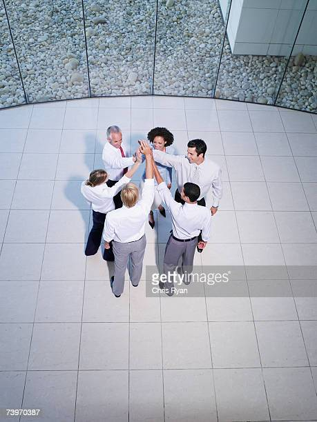 Aerial view of six office workers high fiving each other
