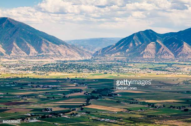 aerial view of small farming town nestled at foot of mountain range - spanish fork utah stock pictures, royalty-free photos & images