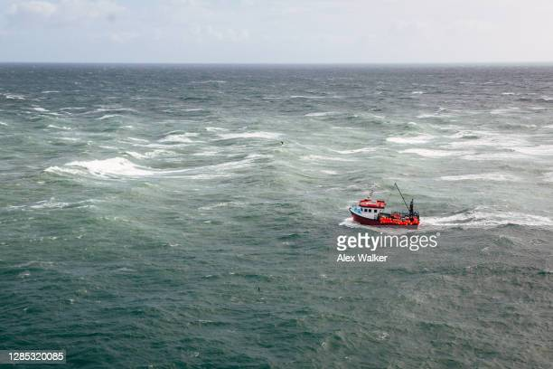 aerial view of small fishing boat in open ocean - nautical vessel stock pictures, royalty-free photos & images