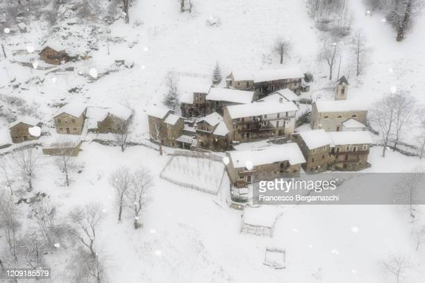 aerial view of small old village covered by deep snow. - italia stock-fotos und bilder