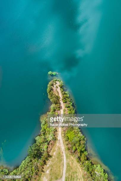 aerial view of small pathway next to lake. - reef stock pictures, royalty-free photos & images