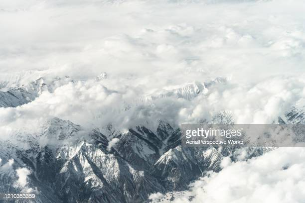 aerial view of snow capped mountains against sky - k2 mountain stock pictures, royalty-free photos & images