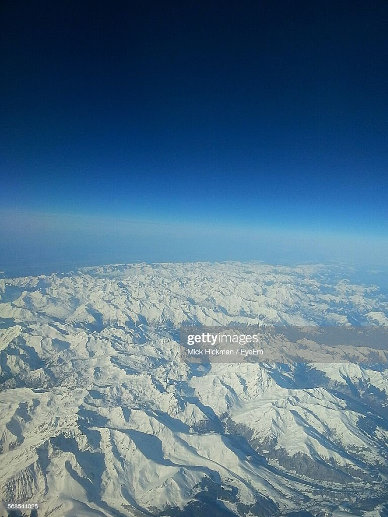 Aerial View Of Snow Covered Mountains Against Blue Sky : Stock Photo