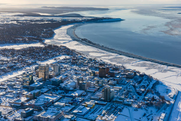 Aerial view of snow covering downtown Anchorage and Cook Inlet at low tide, the Hotel Captain Hook and Conoco Philips buildings in the foreground, Fire Island in the distance, South-central Alaska in winter