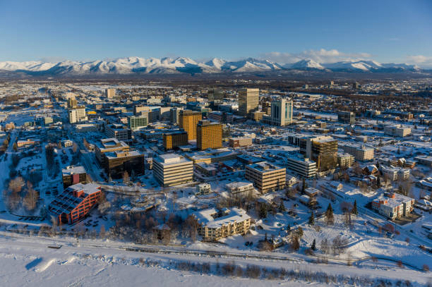 Aerial view of snow covering downtown Anchorage and the the Chugach Mountains in the distance, the Capitan Cook Hotel and Conoco Philips buildings in the foreground, South-central Alaska in winter