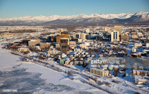Aerial view of snow covering the sea ice on the frozen shores of downtown Anchorage, the Chugach Mountains in the distance beyond the office buildings and hotels, Cook Inlet in the foreground, South-central Alaska in winter