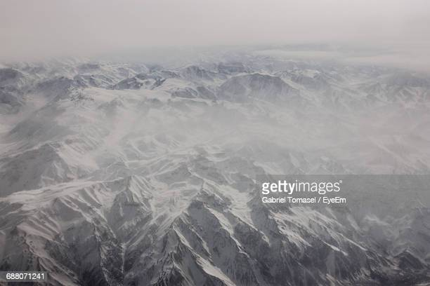 Aerial View Of Snowcapped Mountain Against Sky During Foggy Weather At Verbier