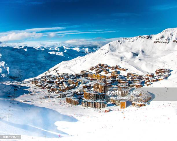 aerial view of snowcapped mountains against blue sky - ski resort stock pictures, royalty-free photos & images