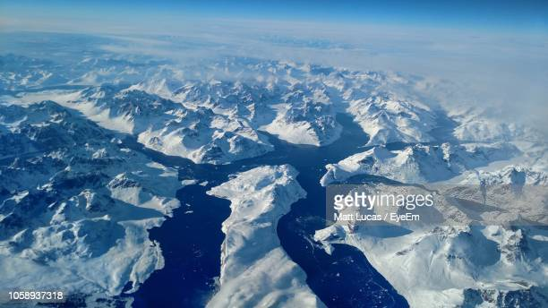 aerial view of snowcapped mountains against sky - north pole stock pictures, royalty-free photos & images