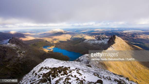 aerial view of snowcapped mountains against sky - snowdonia stock photos and pictures