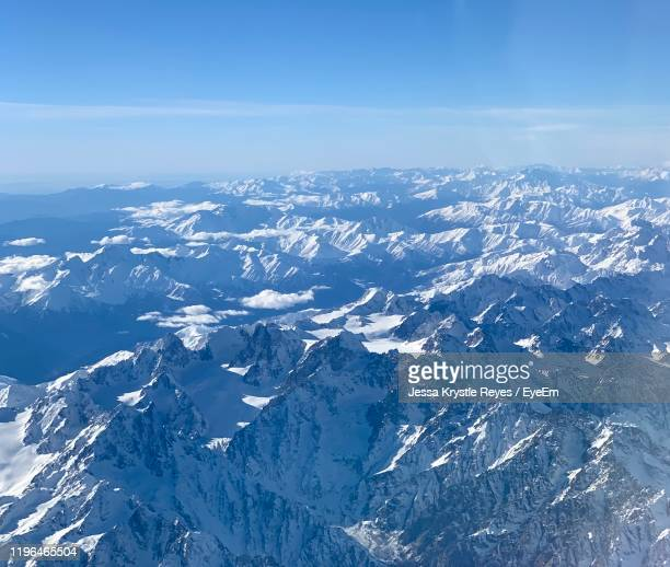aerial view of snowcapped mountains against sky - jessa stock pictures, royalty-free photos & images