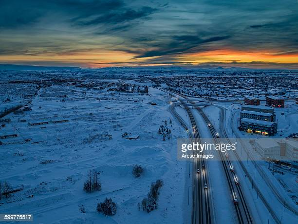 Aerial view of snowy road at sunset.