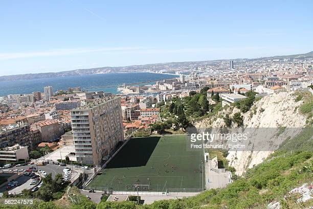 Aerial View Of Soccer Field And Cityscape By Sea Against Blue Sky