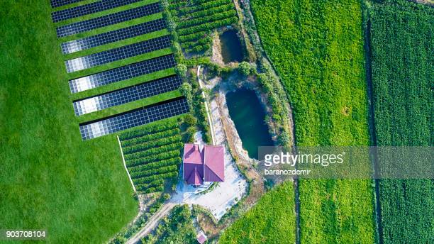 Aerial view of solar energy farm with house and organic farm