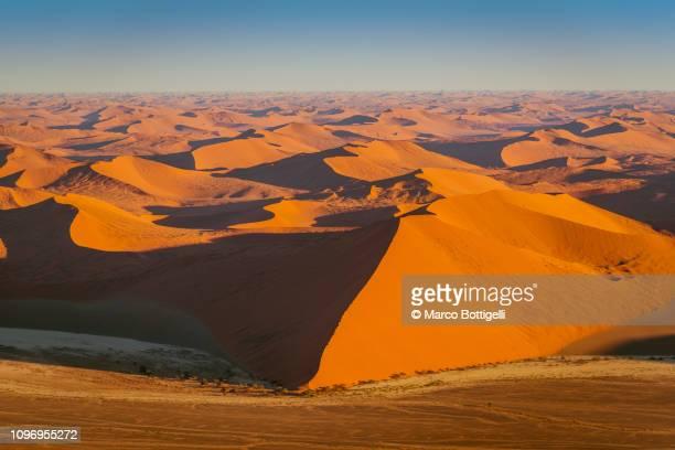 aerial view of sossusvlei red dunes at sunrise, namibia - ナミブ砂漠 ストックフォトと画像