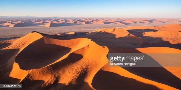 aerial view of sossusvlei red dunes at sunrise, namibia - sossusvlei stockfoto's en -beelden