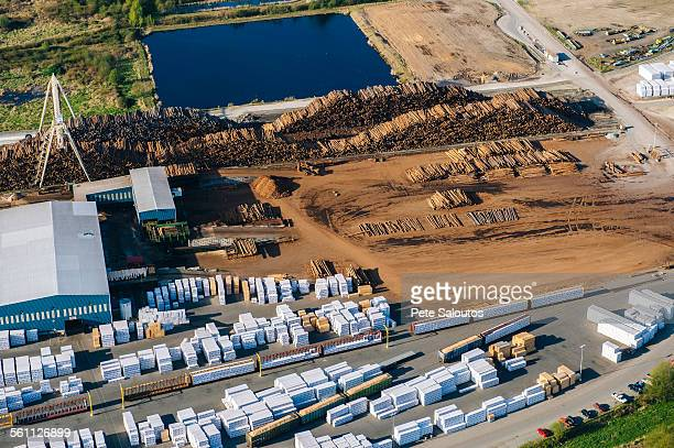 Aerial view of stacked tree trunks and warehouses in timber yard