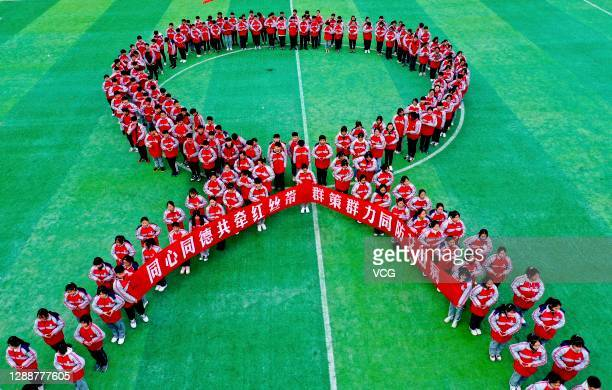 Aerial view of students standing in the shape of a red ribbon to mark the World AIDS Day on December 1, 2020 in Bozhou, Anhui Province of China. The...