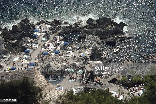 Aerial view of sunbathers and parasols at La Fonteline beach, at the base of the Faraglioni rocks on the island of Capri, Italy, in September 1989.