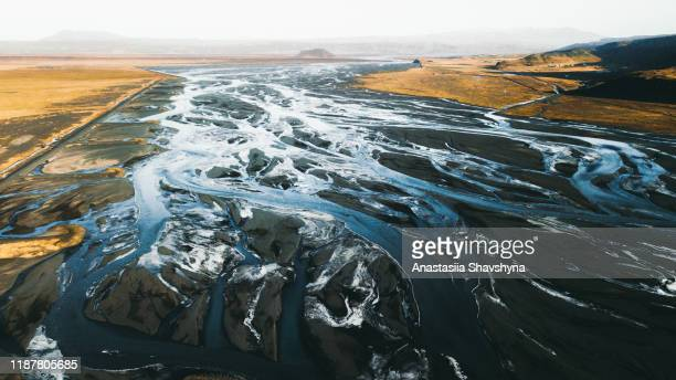 aerial view of sunrise above glacial rivers, road and mountains in south iceland - eroded stock pictures, royalty-free photos & images