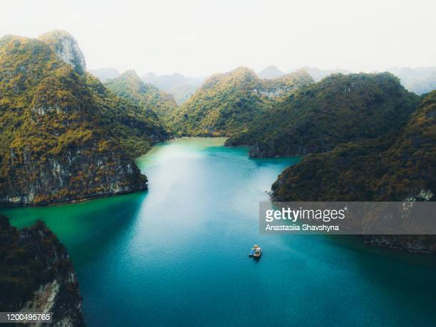 aerial view of sunset above group of small tropical islands in the turquoise sea in vietnam - halong bay stock pictures, royalty-free photos & images