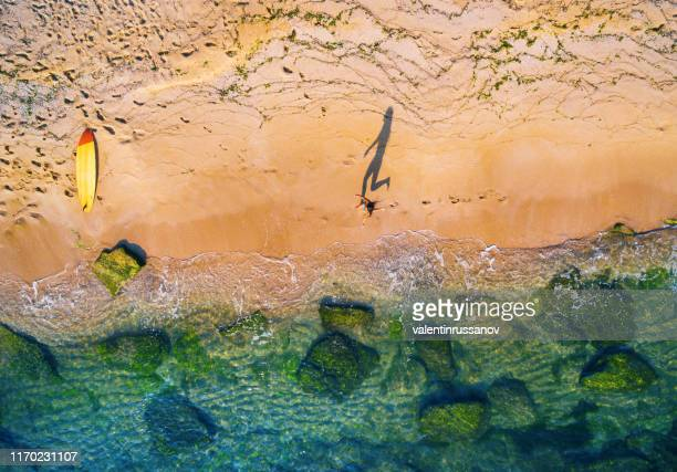 aerial view of surfer going into the sea - gold coast stock pictures, royalty-free photos & images